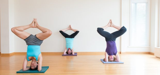 three woman in butterfly headstand.